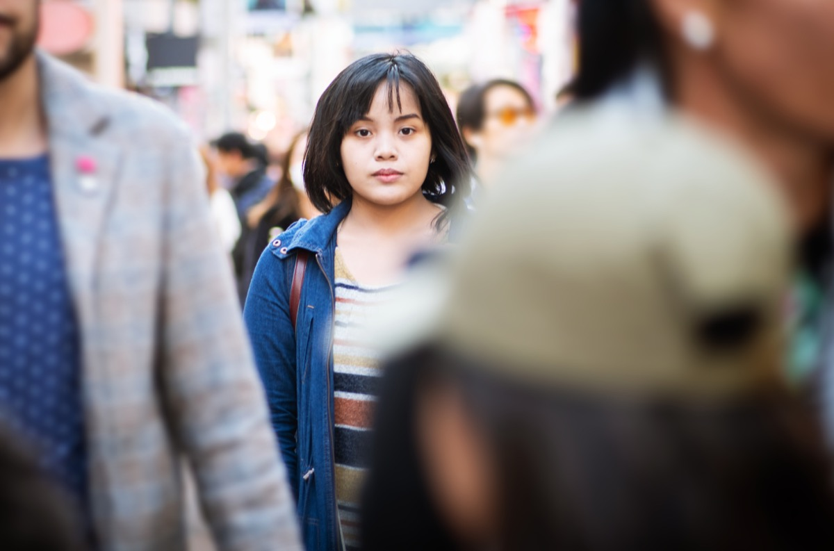 A young woman standing in the middle of a crowded street, looking at the camera.