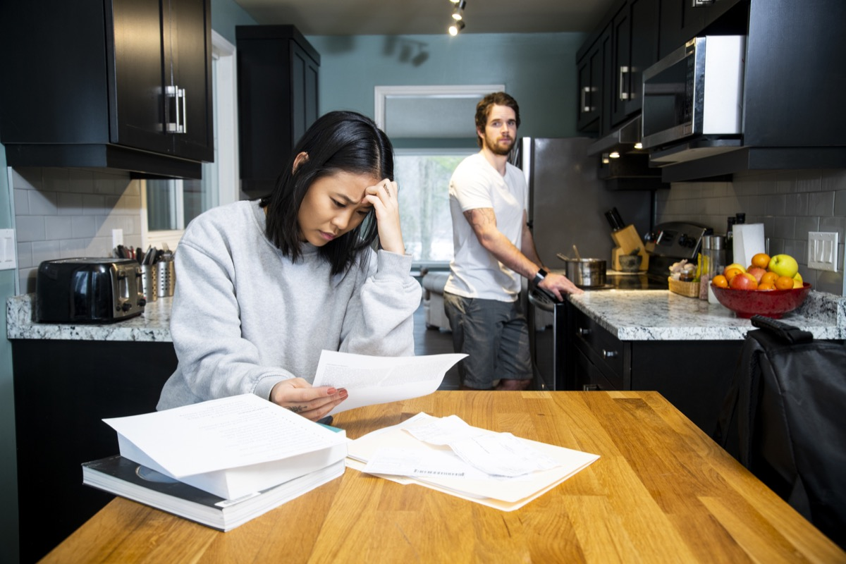 A female student worrying about financial issues at home in her apartment with her male friend cooking at the stove.