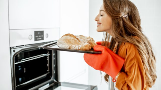 Beautiful young woman baking bread in the oven at the modern white kitchen at home