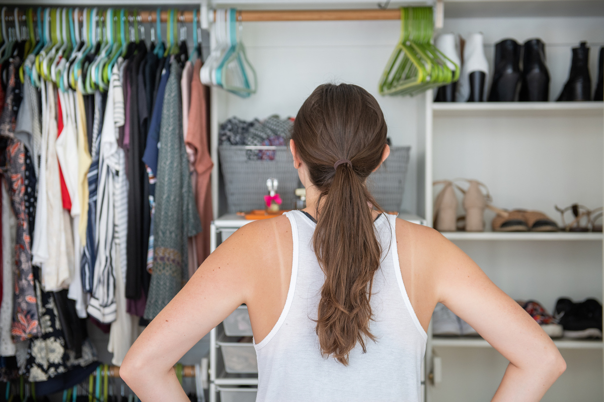 Young woman with her hands on her hips trying to decide what to wear from her well organized closet