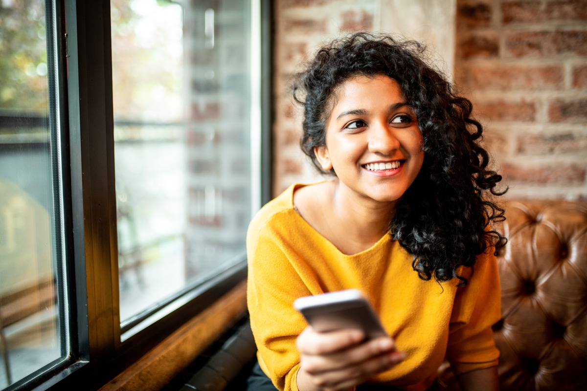 young woman smiling while using her phone