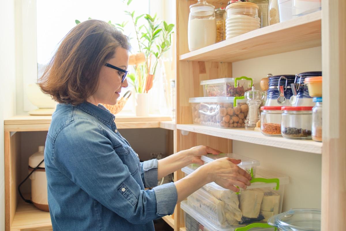 white woman taking box off shelf