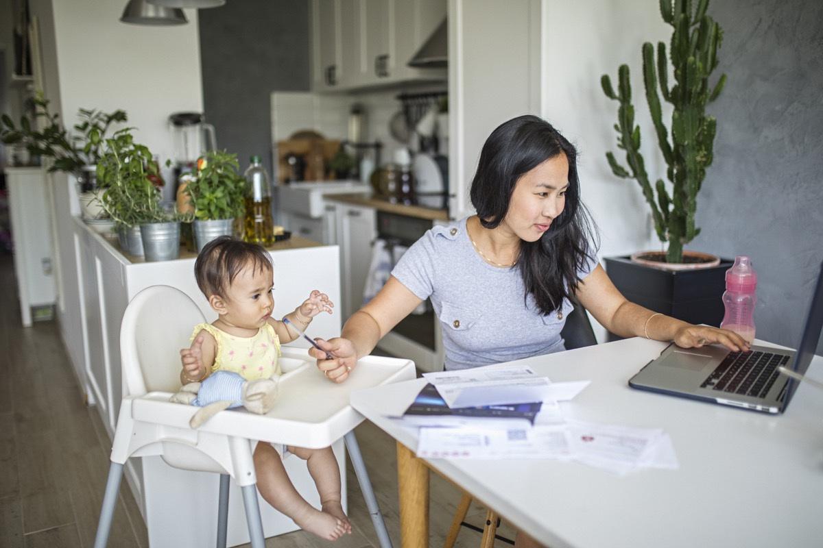 Young mother working and spending time with baby at home