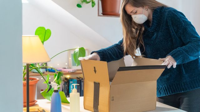 woman in coronavirus mask opening package