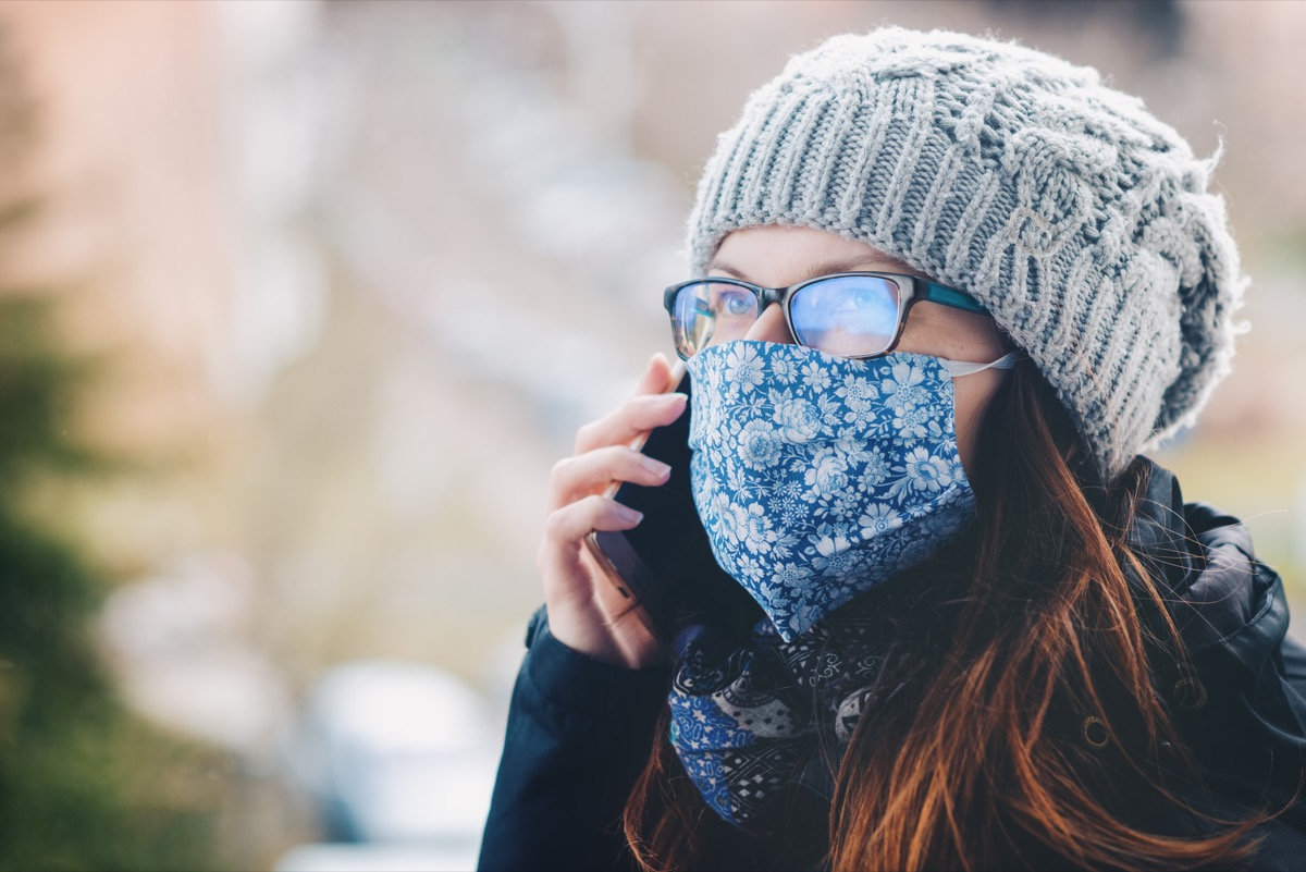 white woman on cell phone wearing cloth face mask