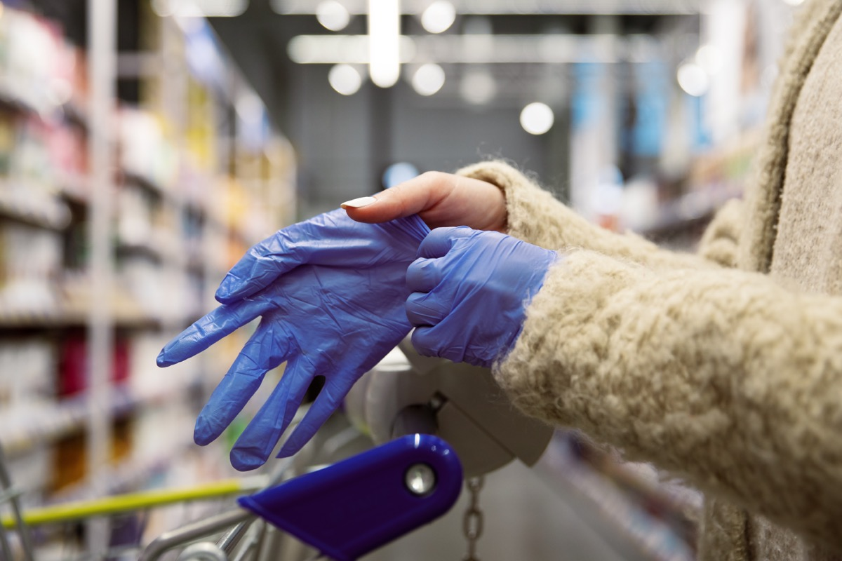 woman putting on gloves in supermarket aisle