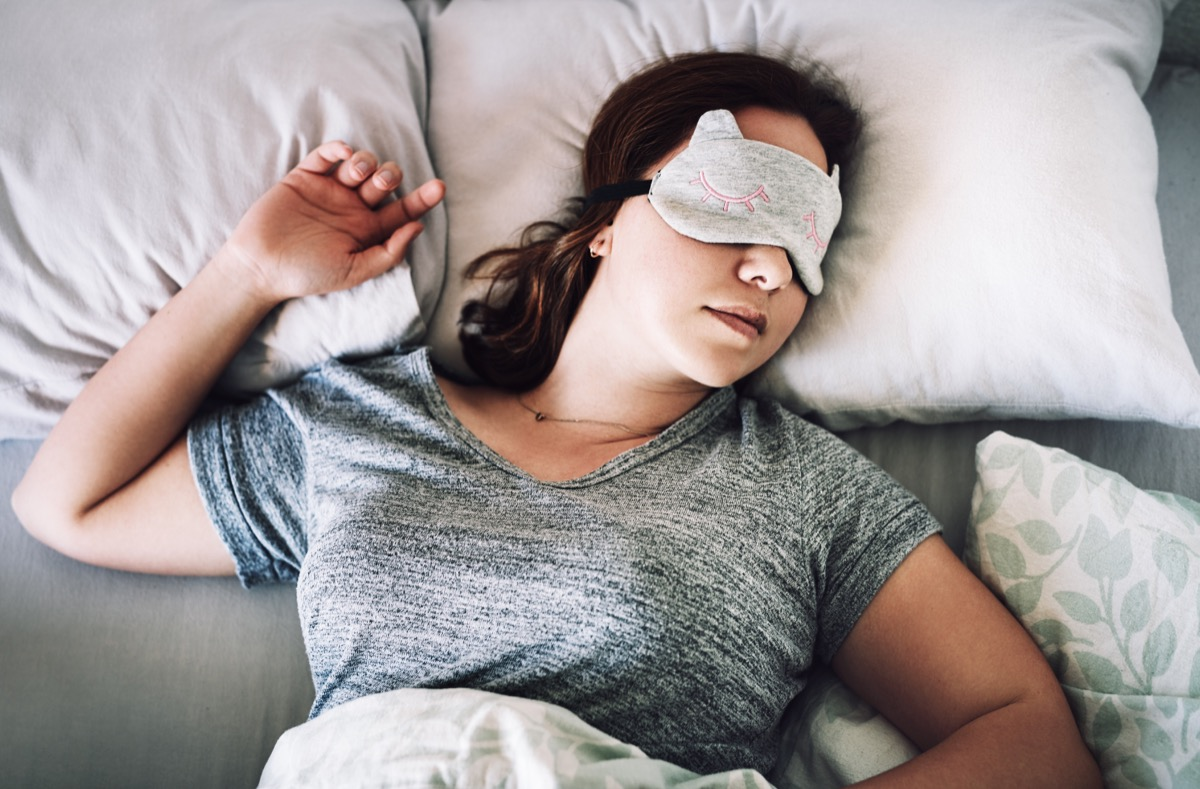 High angle shot of an attractive young woman sleeping with a mask on her face in her bedroom at home
