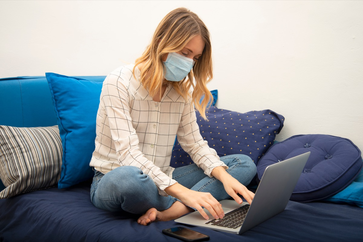 young white woman working from home wearing mask