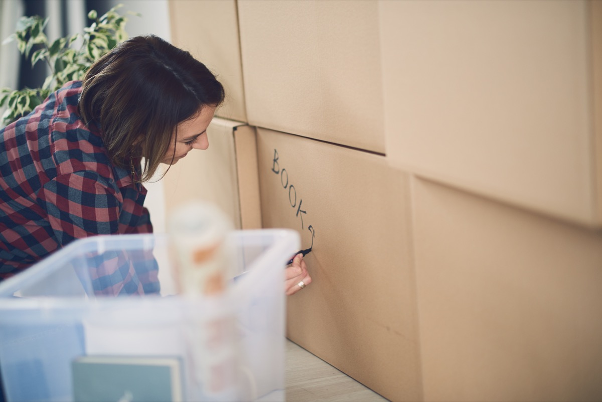 white woman writing on cardboard boxes