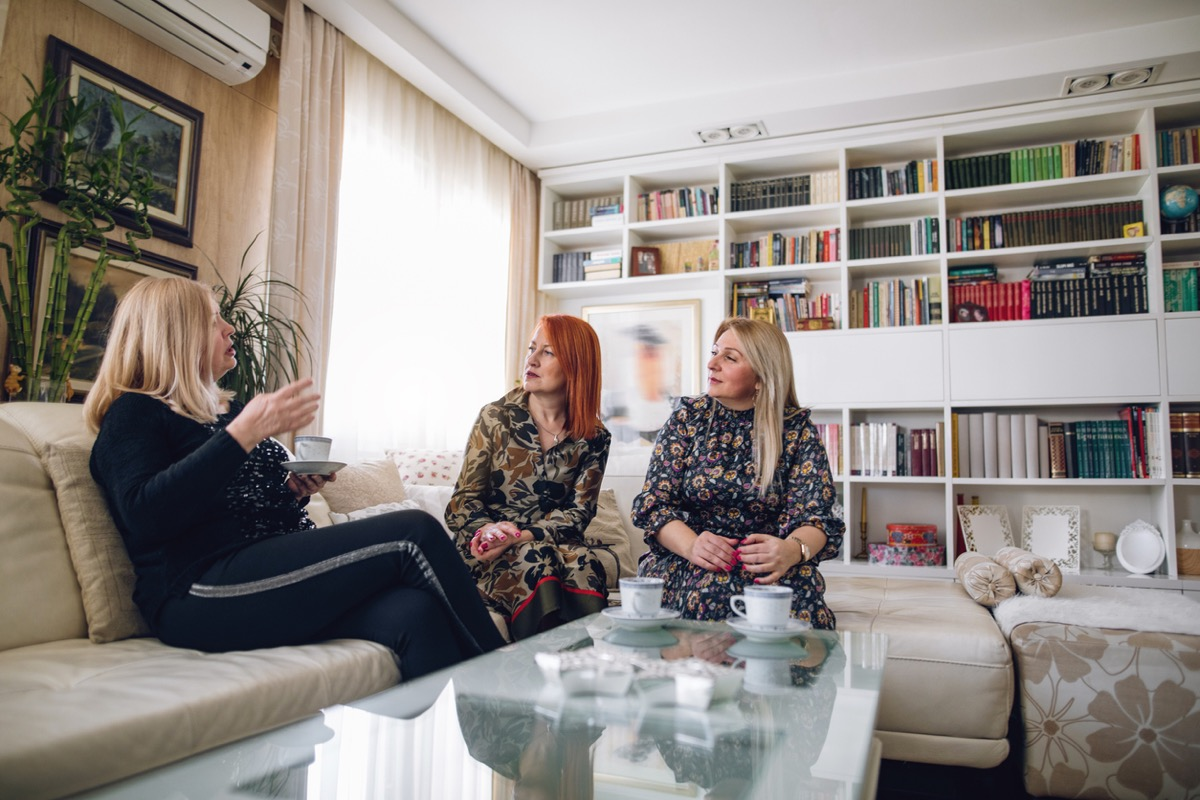 three mature women enjoying their time together at home, drinking coffee.