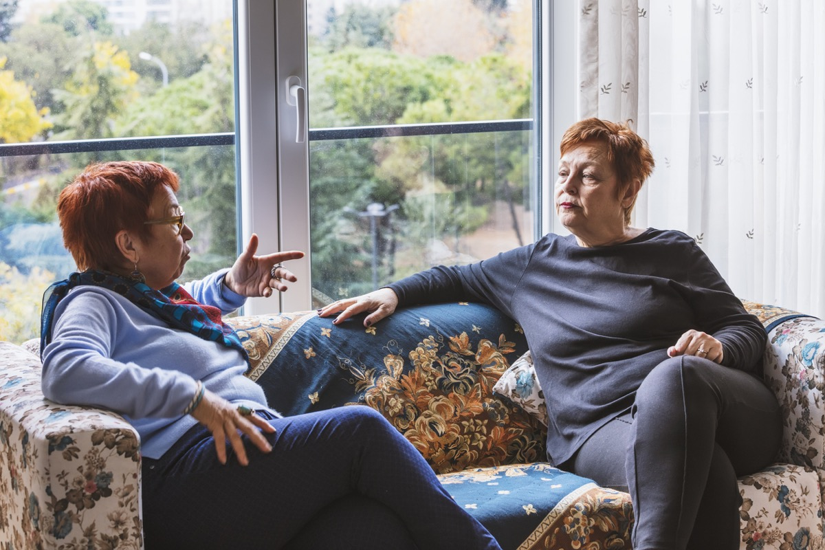 Mature women with short red hair talking on couch