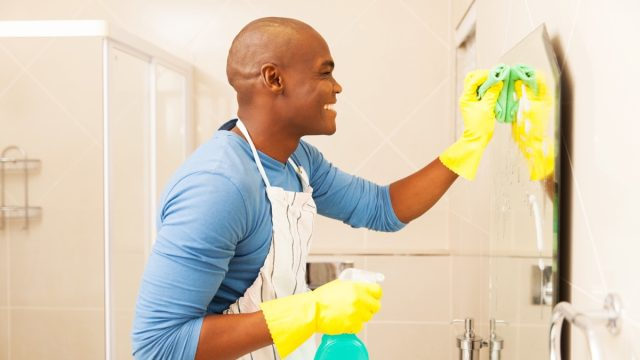 young happy black man cleaning bathroom mirror