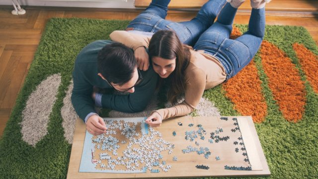 young white couple doing jigsaw puzzle on floor