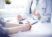 Closeup of woman doctor and woman patient sitting at the desk and talking