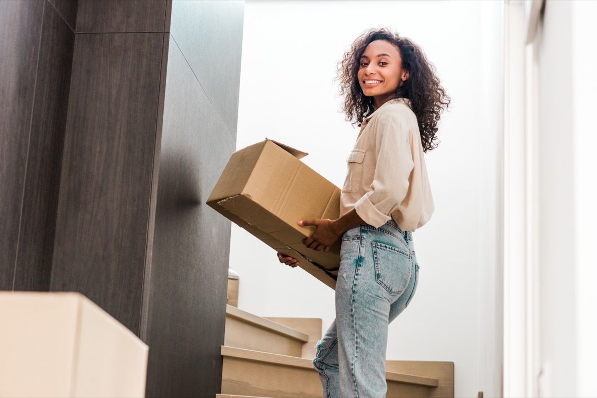 young black woman moving cardboard box upstairs