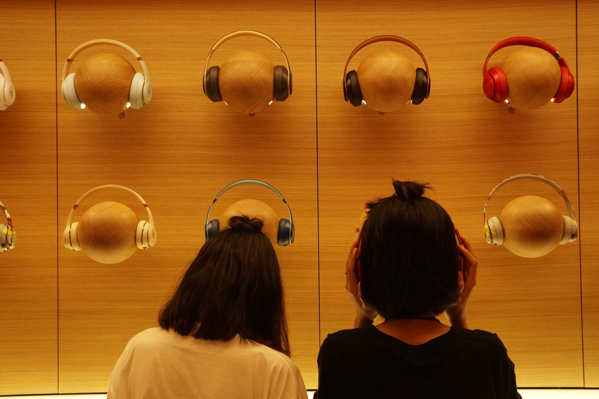 Girls trying on headphones at Apple store