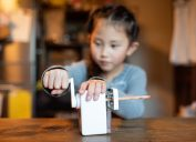 Asian girl sharpening a pencil