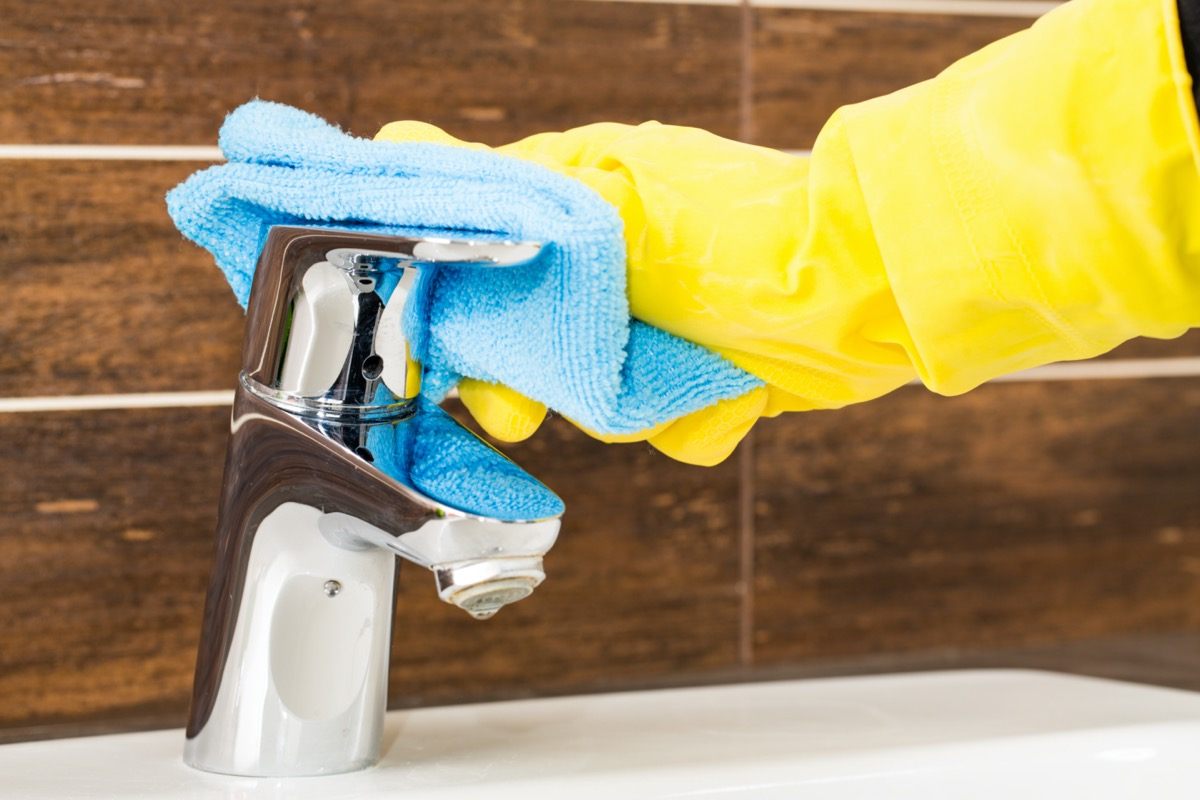 Gloved hand cleaning bathroom faucet