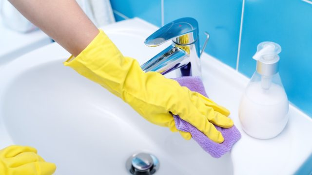 Person wearing gloves and cleaning bathroom sink