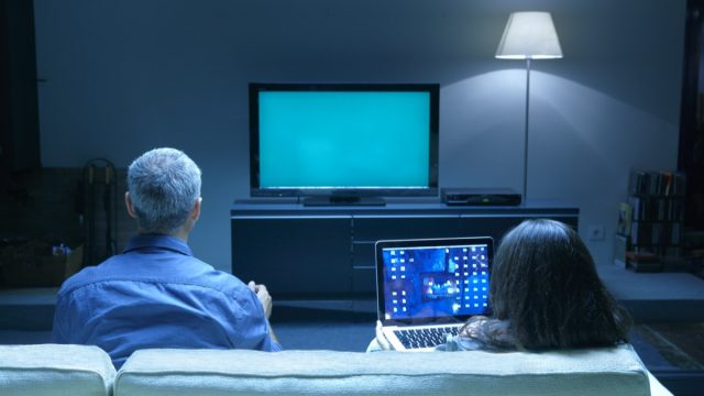 Mature couple watching TV and looking at laptop