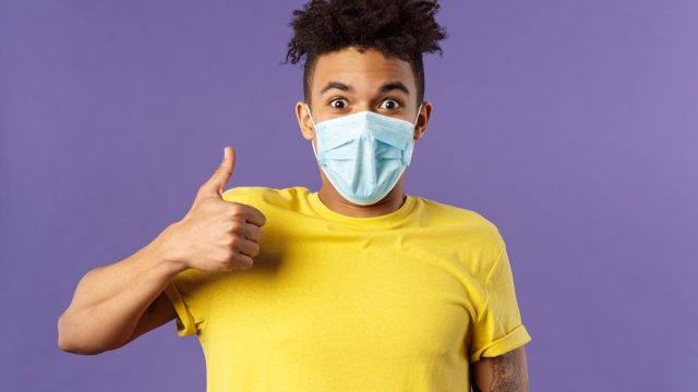 Man giving thumbs up, wearing mask