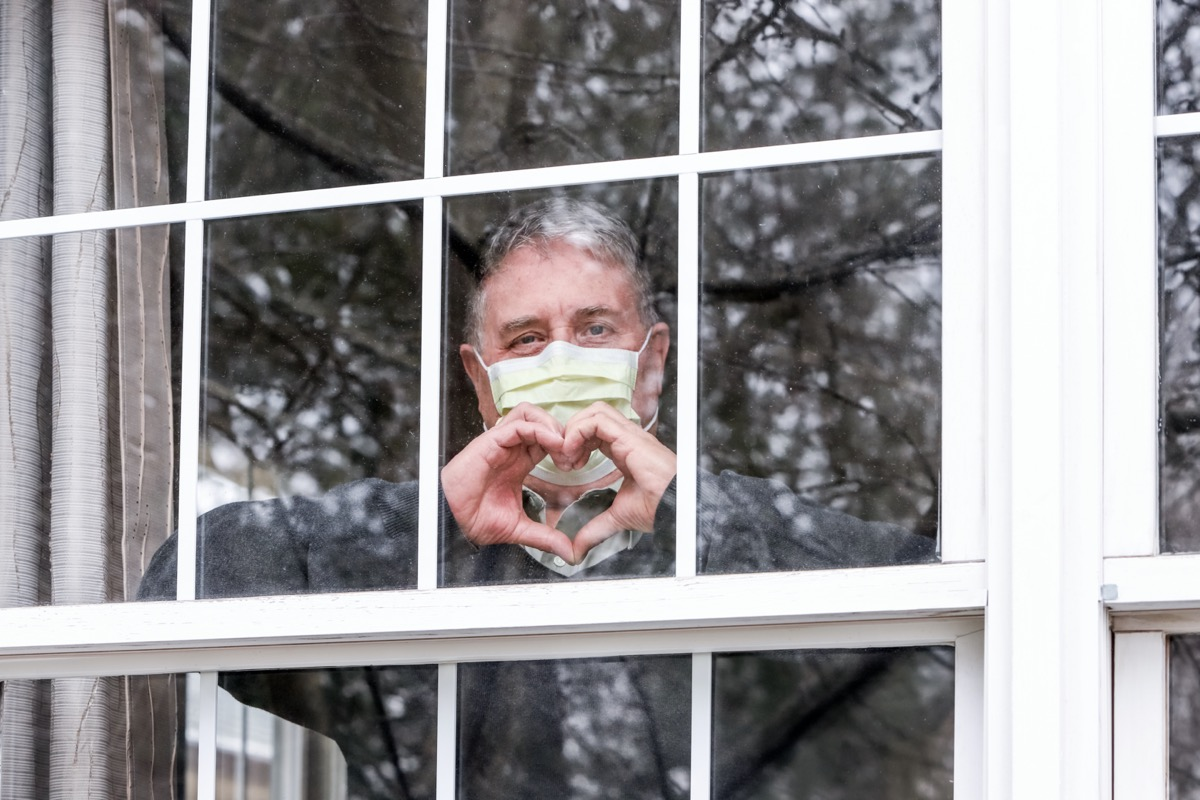 Senior man wearing mask and standing in window
