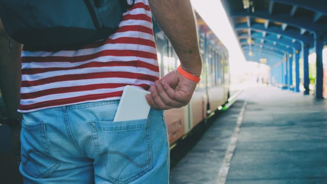 Man in train station with phone in back pocket