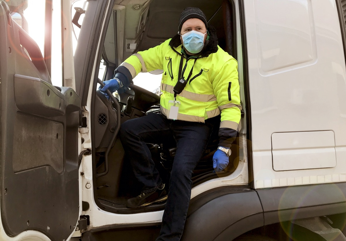 Man driving truck while wearing mask and gloves
