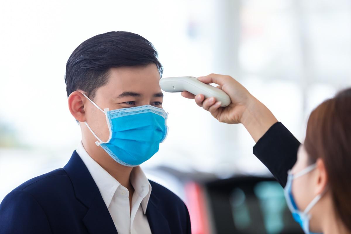 Woman taking man's temperature