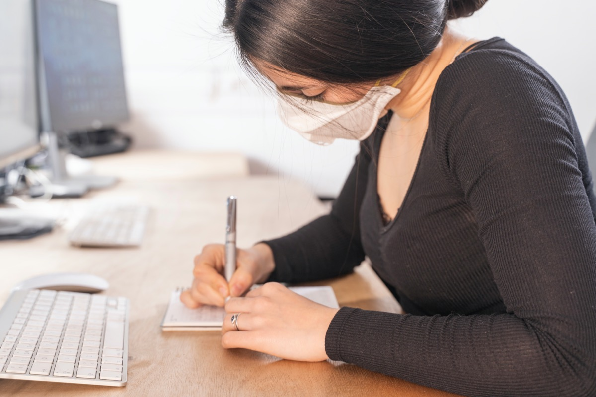 Woman sitting at desk and writing in notebook while wearing mask