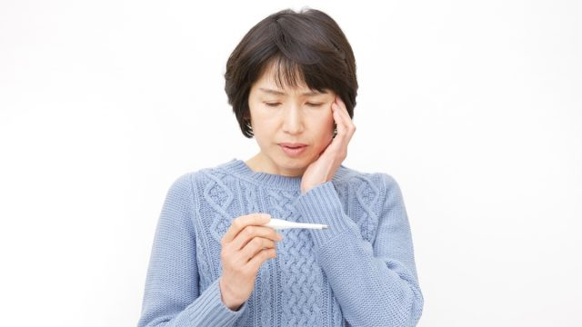 Asian woman taking her own temperature