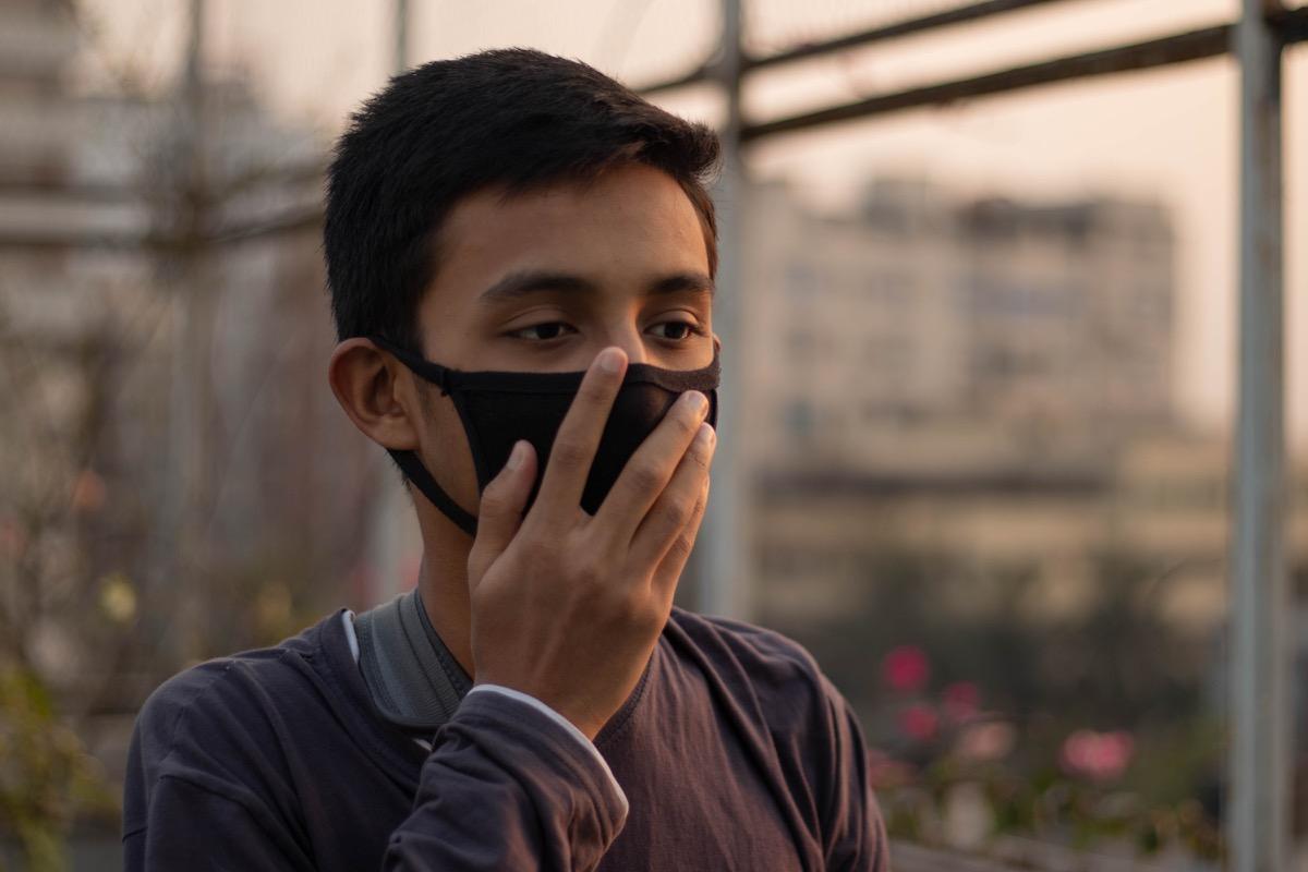 Young boy adjusting mask