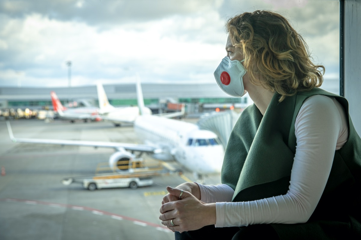 woman wearing a mask looks out the window at an airport