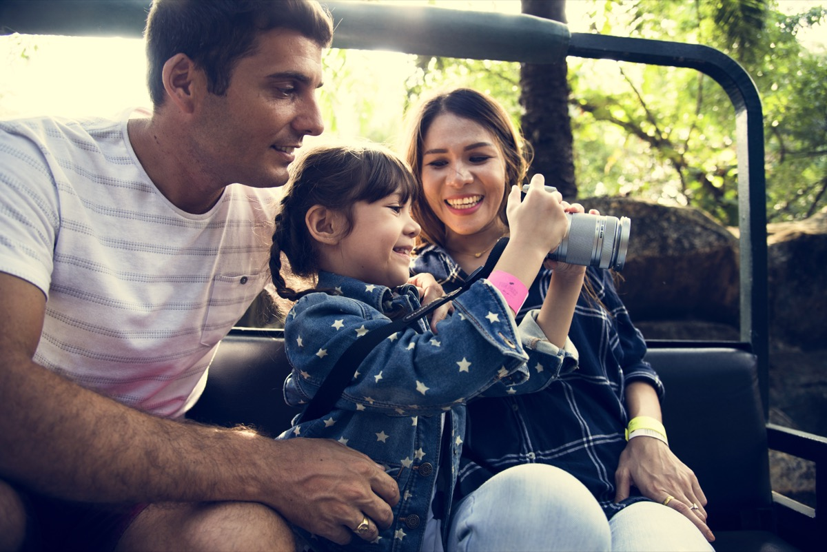 parents and daughter in golf cart taking photos on safari vacation