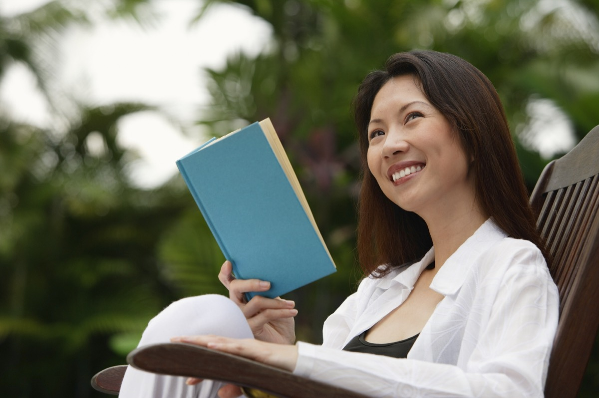 30-something asian woman reading a book outdoors