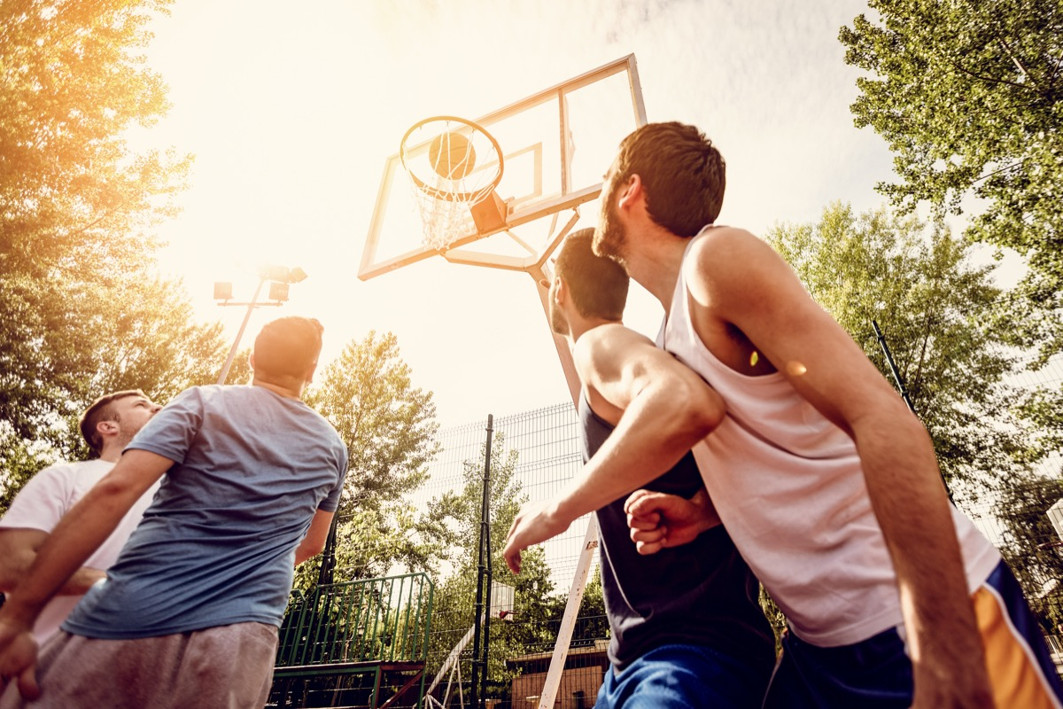 four men play basketball outdoors