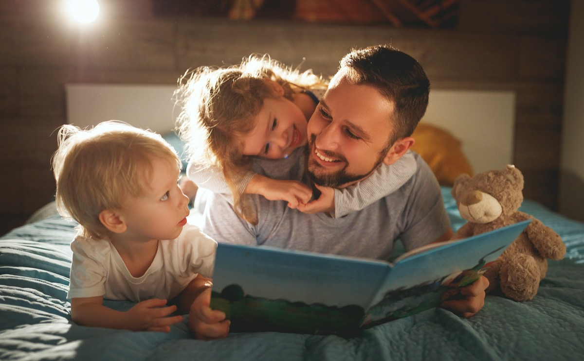 dad reads a bedtime story to his two kids