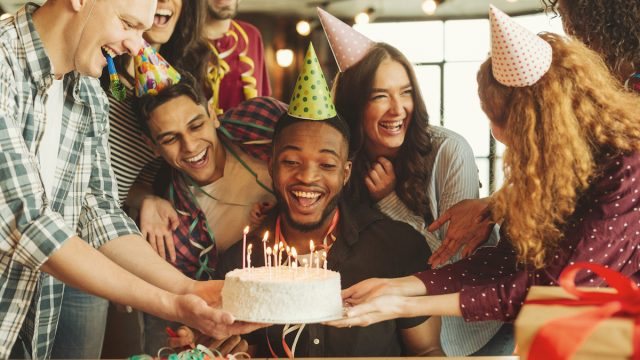 Happy black man celebrating his birthday, looking at cake with candles, surrounded by friends