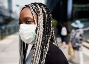 black woman with braids standing outside wearing face mask