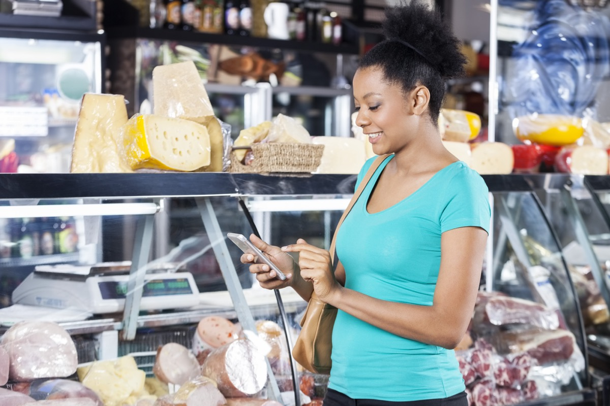 young black woman using cell phone in grocery store