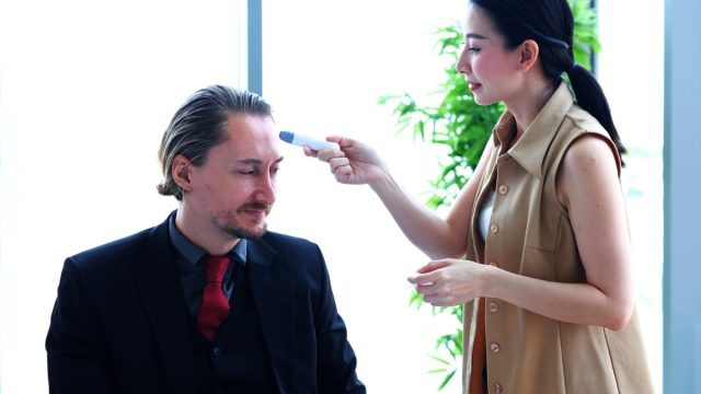 young asian woman giving white male employee temperature check for coronavirus