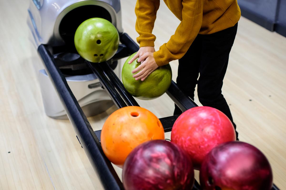 closeup of hands grabbing ball at bowling alley