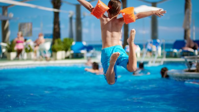 young white boy in swimmies jumping into pool