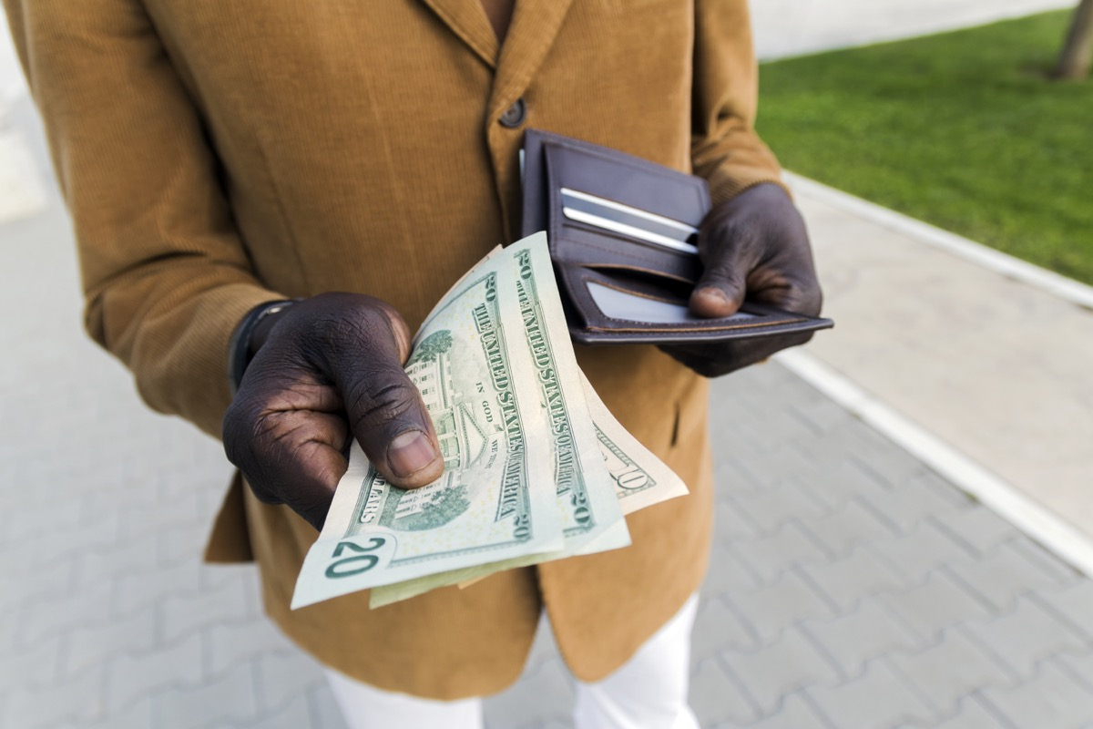 Cropped shot of businessman gets money from the wallet. Purse with dollars in their hands. Businessman's hand in suit takes out dollar money from a wallet