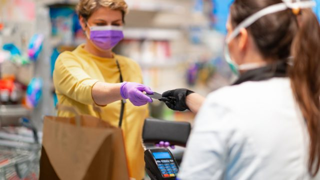 A cashier wearing gloves and a face mask hands a customer back wearing a face mask her credit card