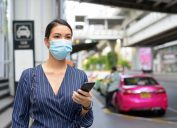 Woman in face mask holding phone in public