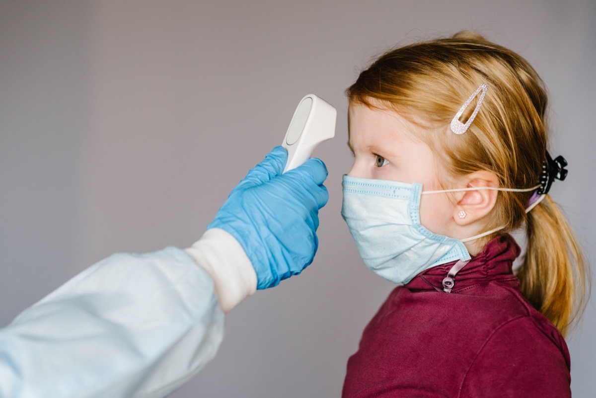 doctor or nurse with gloved hands checking little girl's temperature
