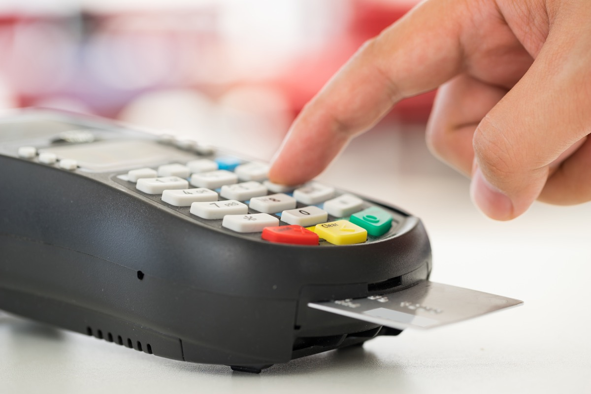 white hand using chip credit card reader