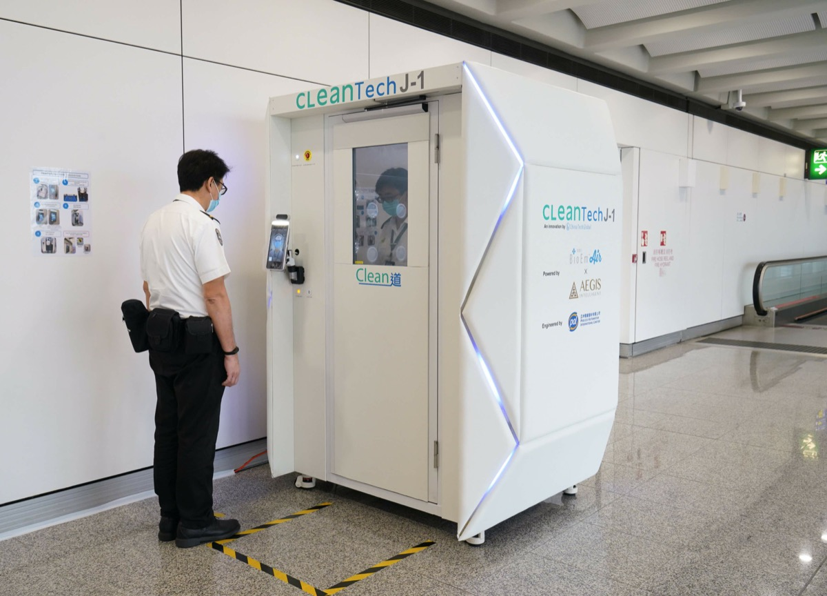 airport security steps into a health screening booth