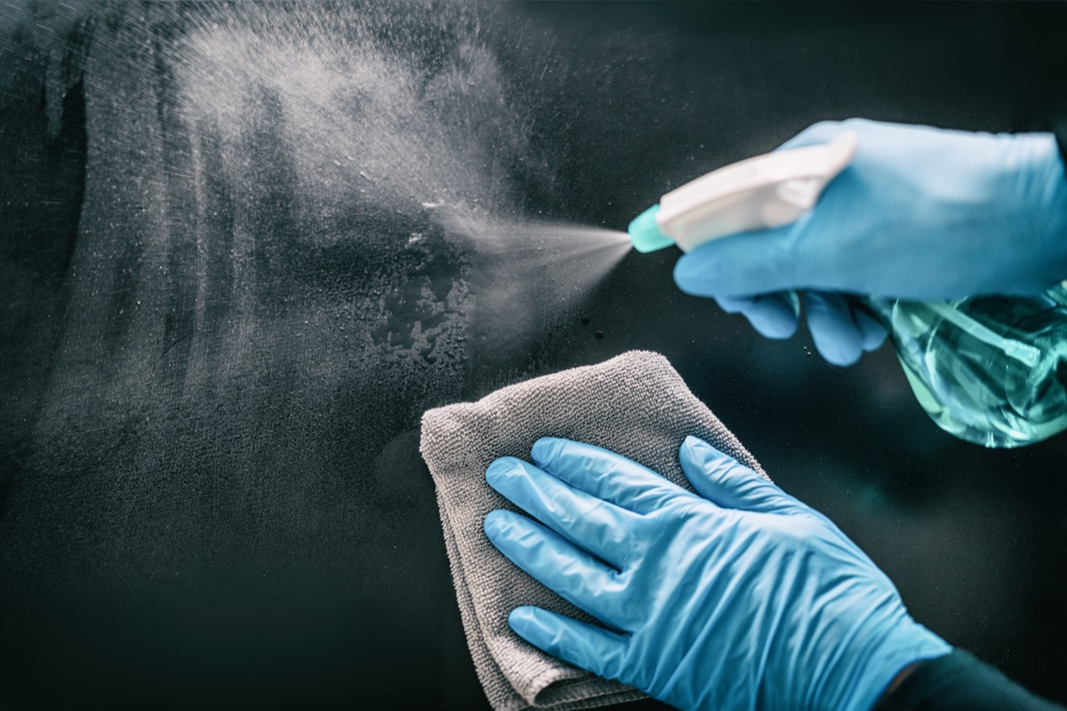 hands in blue nitrile gloves cleaning surface